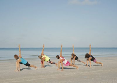 group yoga on beach_wholesome life retreats